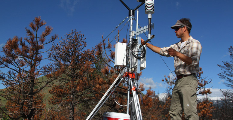 An NCAR scientist with a weather monitoring station
