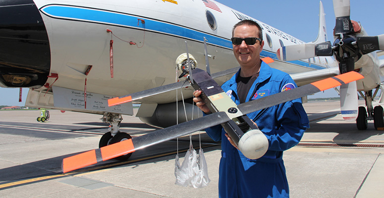 "NOAA scientist Joe Cione, lead author of a new paper on using disposable drones for hurricane observations, holds a Coyote drone in front of a NOAA P-3 ""hurricane hunter"" research aircraft at McDill Air Force Base in Tampa, Fla."