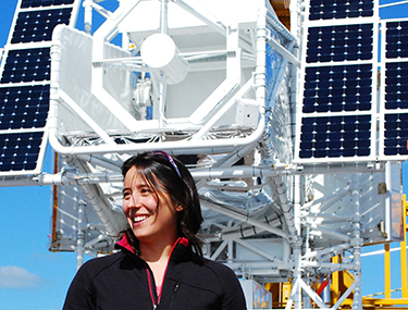 Image of Rebecca Centeno Elliott, and a satellite with solar panels behind her.