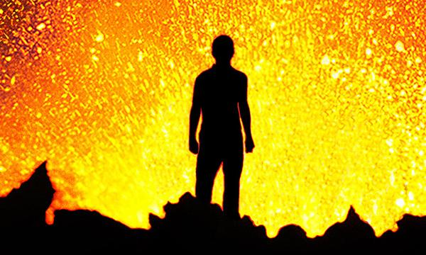 silhouette of person standing in front of a volcanic eruption. Yellow lava flares in front of him.