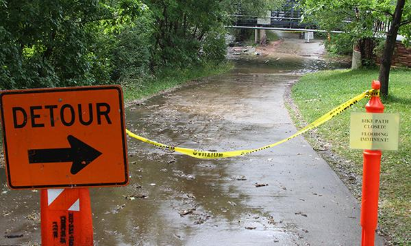A detour sign and a caution tape block the bike path due to imminent flooding of the Boulder Creek.
