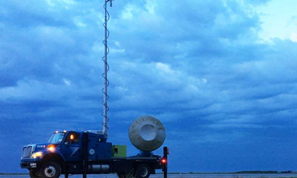 A Doppler on Wheels (DOW) sits in the foreground with an overcast sky in the background.