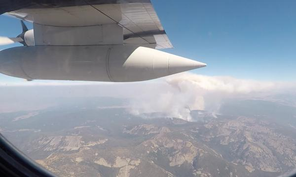 The wing of the C-130 aircraft is seen through the window in the foreground, with a wildfire and smoke plume coming up from a set of mountains in the background.