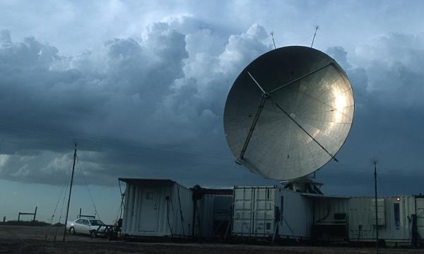 Image of a large ground radar placed above large metal containers. Clouds in the background indicate a looming storm.