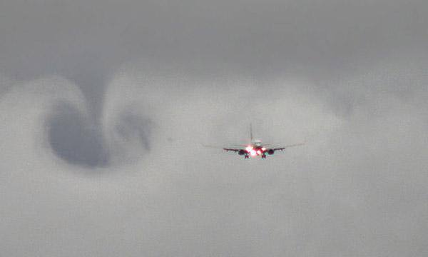 A plane coming in for a landing on a cloudy day