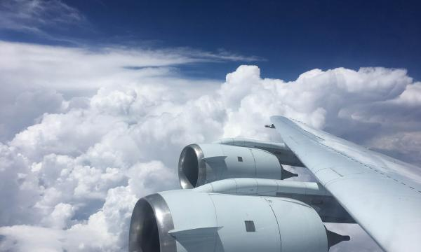 Image of an aircraft wing and engines flying over cumulonimbus clouds.