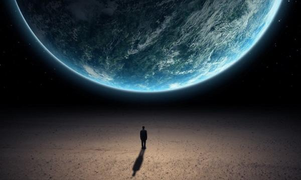 Silhouette of a man standing below a large image of the world.