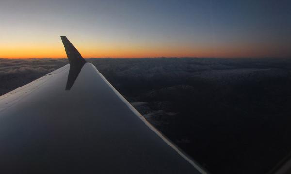 Looking down the wing of a plane during flight over Antarctica at sunset