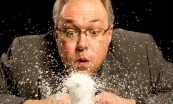 Image of Jo Hecker blowing snow out of a cup filled with snow.