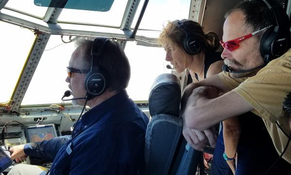WE-CAN scientists in the cockpit of the NCAR/NSF C-130 talk with the pilot during a research mission to study western U.S. wildfires.