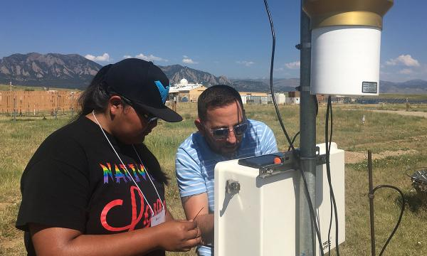 Student and mentor work together to install an instrument that measures wind speeds out in a field