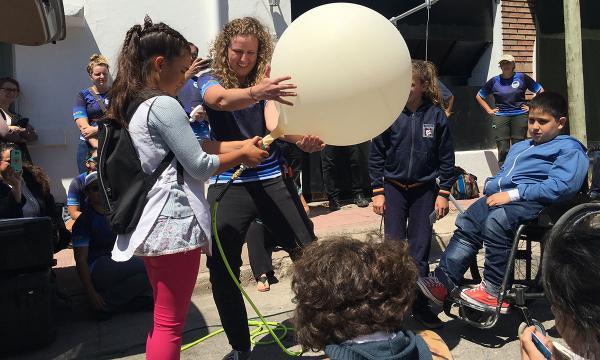 Un científico trabaja con jóvenes estudiantes en Argentina para preparar un globo meteorológico para su lanzamiento.