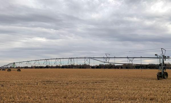 A center-pivot irrigation system in a brown field against a cloudy sky